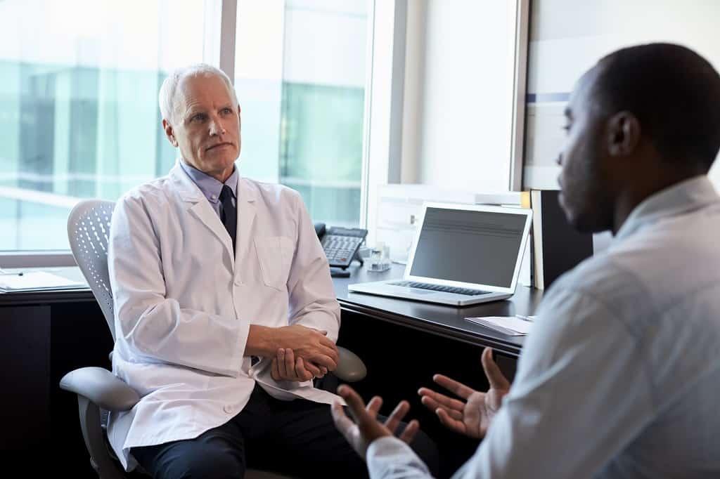 Vasectomia aumenta o risco de câncer de próstata - Médicos no consultório discutindo sobre essa possibilidade