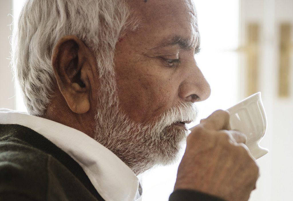 Idoso com dores causadas por um cálculo renal consumindo chá de quebra pedra