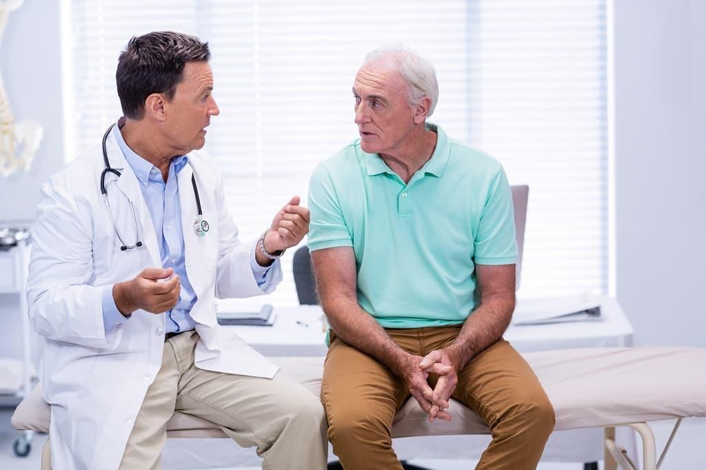 consulta periódica Médico Especialista em cirurgia robótica para câncer de próstata instruindo paciente sobre os cuidados em uma consulta periódica