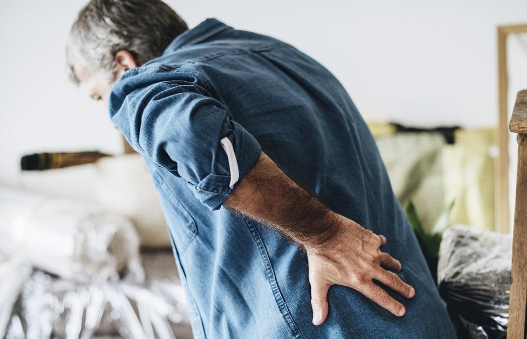 Homem de idade sofrendo com dores por conta da pedras nos rins