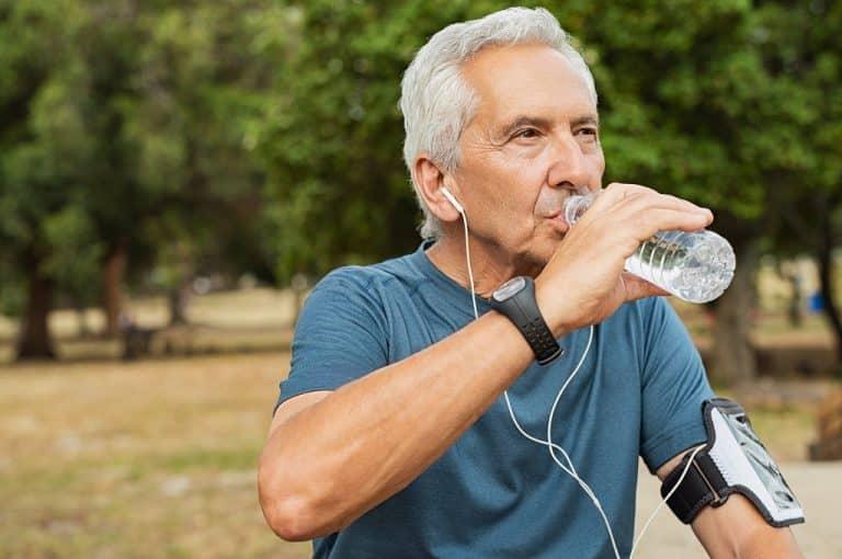 Homem de idade tomando água seguindo as dicas de um médico urologista especialista em Cirurgia de Pedras nos Rins a Laser