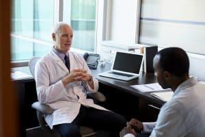Homem se consultando com um médico sobre os mitos do câncer de próstata