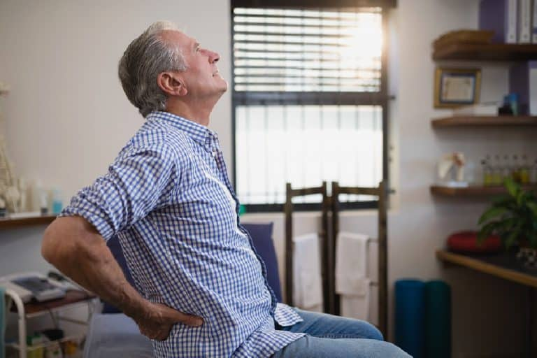 Senhor de idade apresentando alguns dos sintomas de cálculo renal